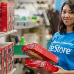 ReStore employee stocking a shelf with boxed merchandise and smiling